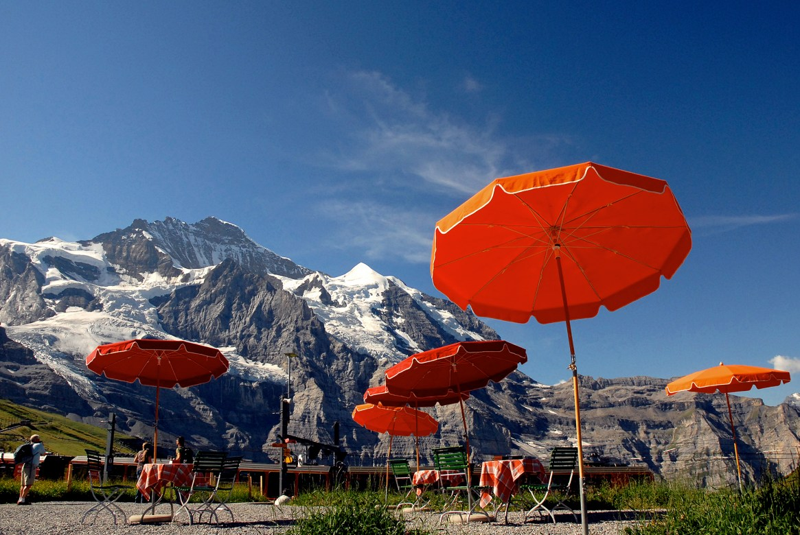 Orange umbrellas seen against snowy mountains at Kleine Scheidegg, Jungfrau region, Switzerland