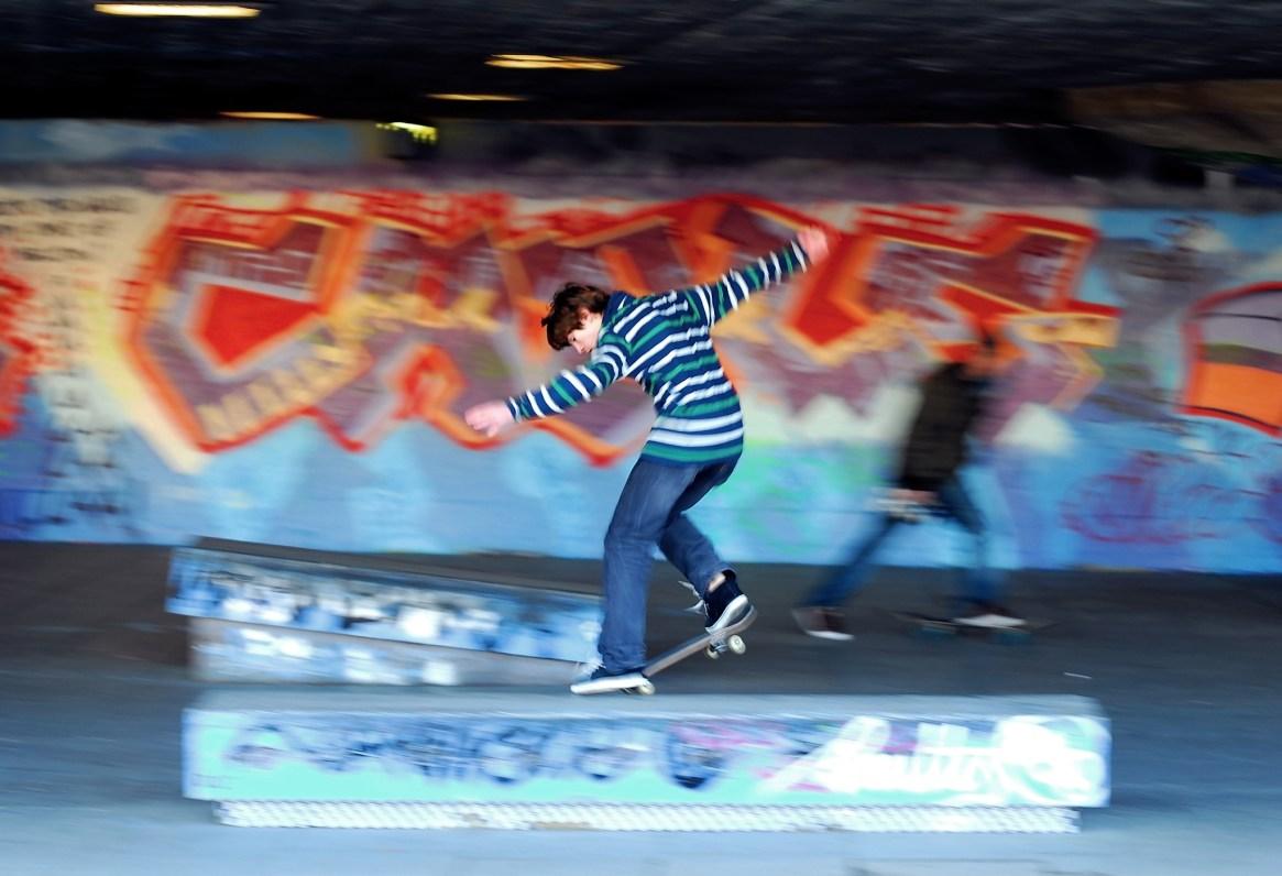 A boy skateboards past orange graffiti