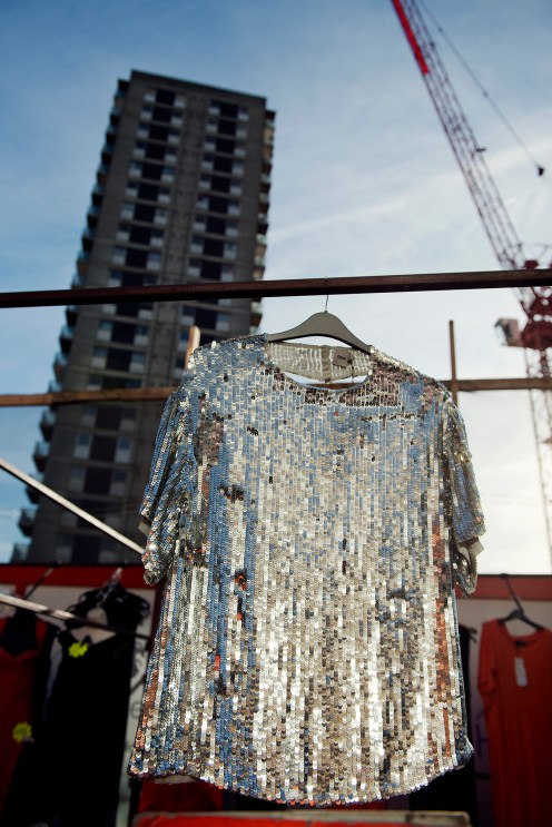Silver sequins top hanging from a rail at street market