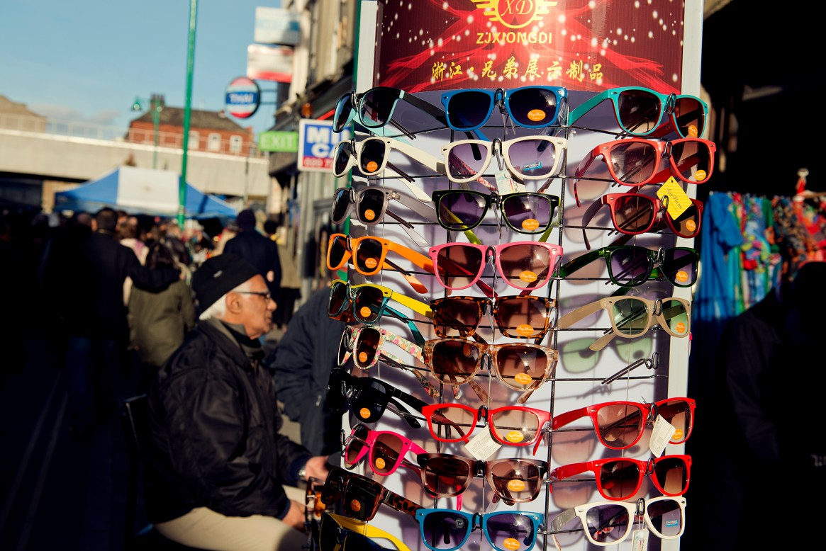 Sunglass stand and old man looking on