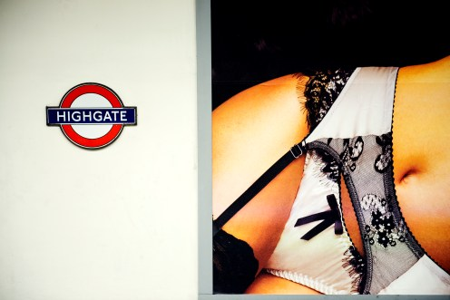 Tube sign for highgate and poster showing a woman wearing underwear