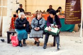 Three old woman chatting whilst sat on a bench in the street