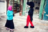 A woman in wearing the hijab looks at a person dressed as Mickey Mouse
