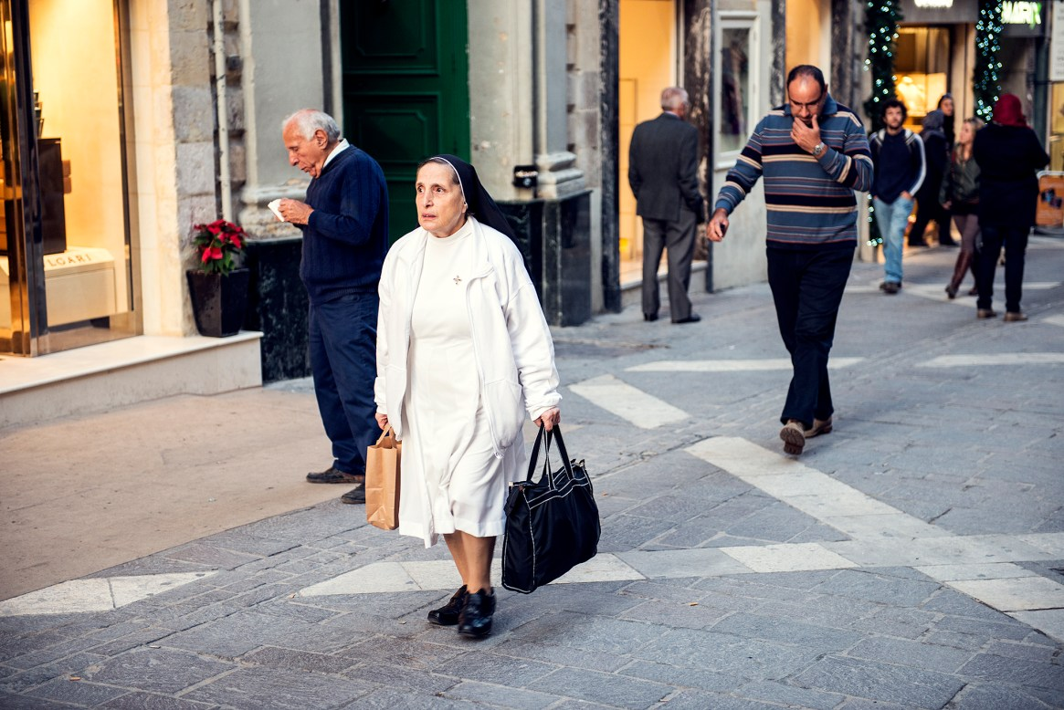 Nun dressed in white with black bag