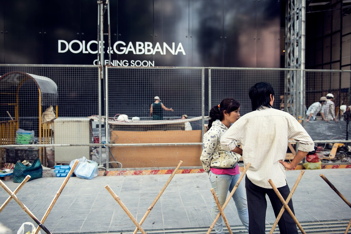 People standing in front of a renovation sign saying Dolce & Gabbana - Coming Soon