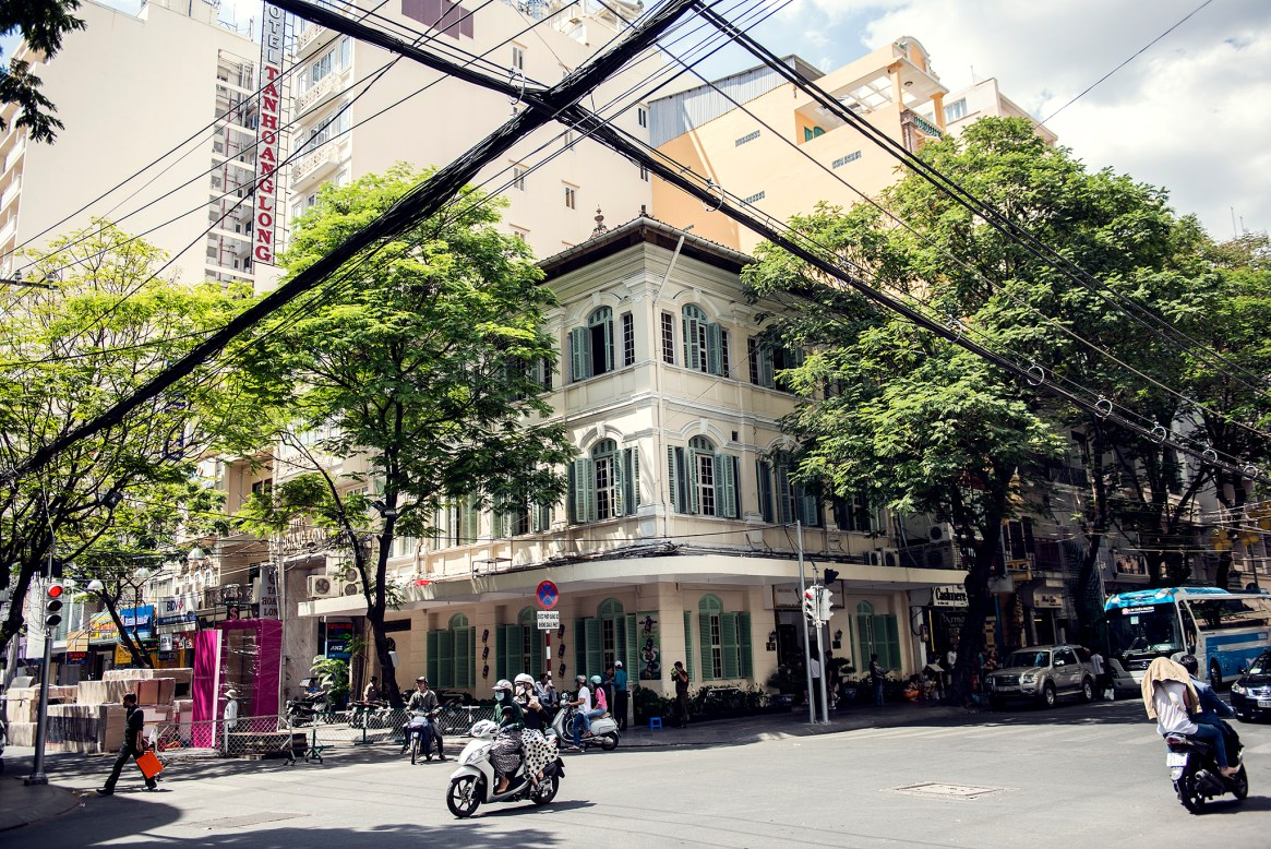Man riding his bike across an elegant intersection in District 1, Ho Chi Minh City