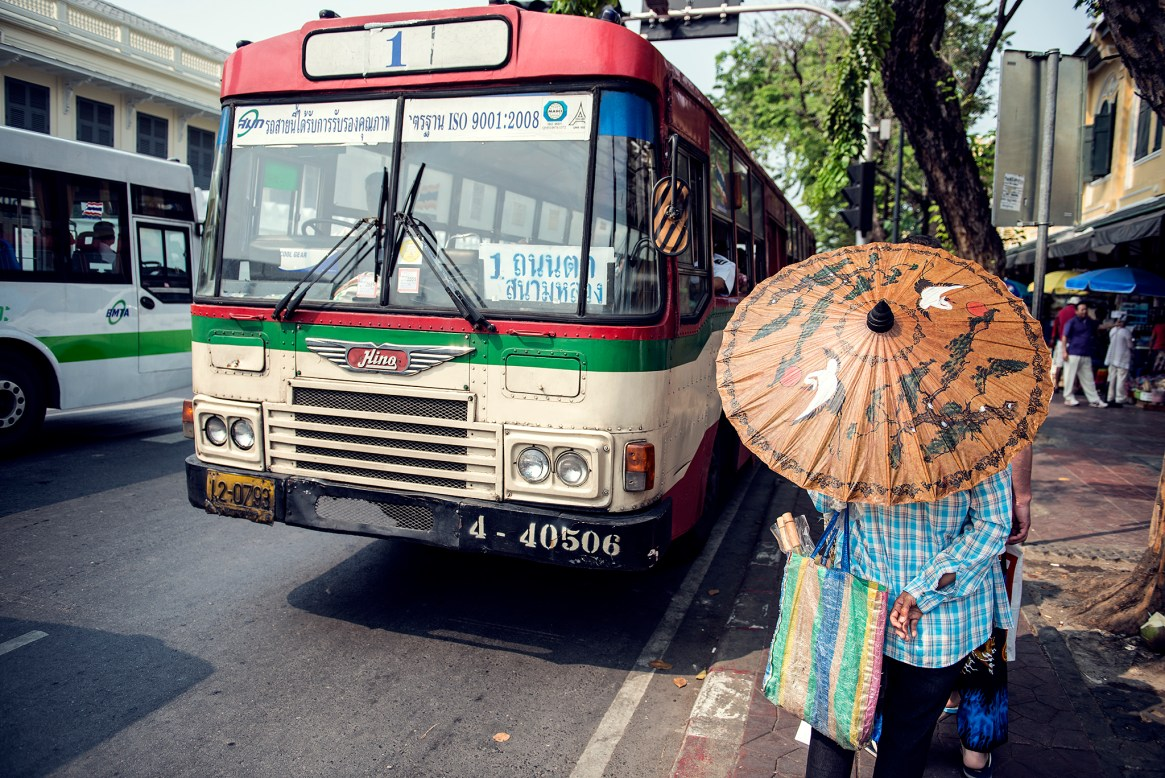 Thai woman with a colourful, traditional umbrella waits for the bus in Bangkok, Thailand