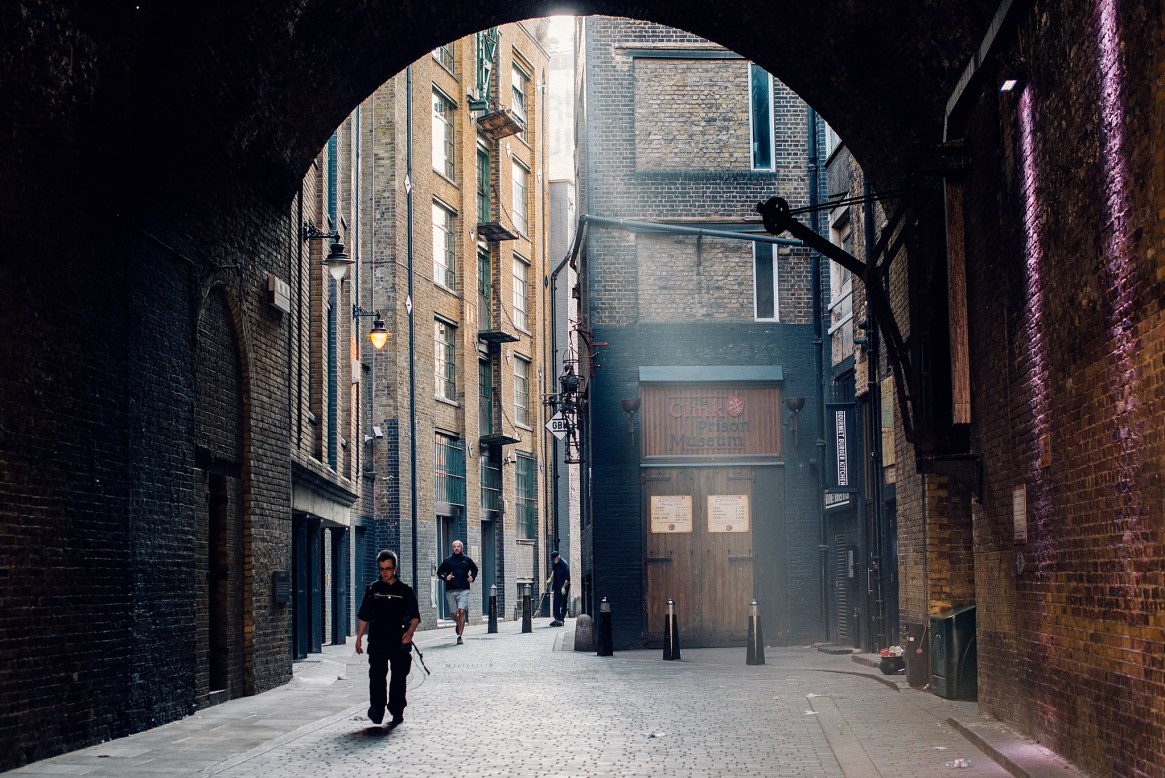 Low key shot of railway arch and rays of sunlight above The Clink in Southwark, London