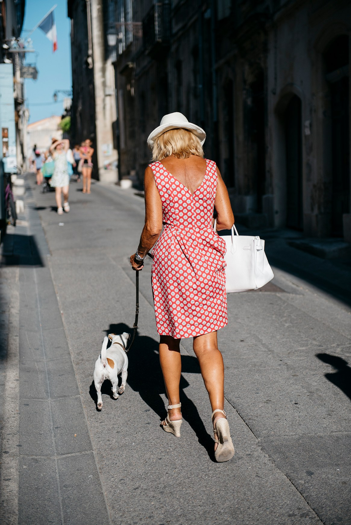 A woman wearing a striking, stylish red-and-white dress with white shoes, hat and handbag is seen from the back as she walks down the street with her little white dog at Les Rencontres d'Arles photography festival, Arles, France