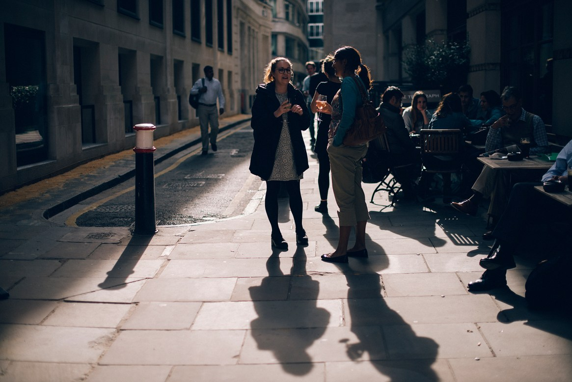 Two women have a drink outside a pub in the City of London after work on a sunny summer's evening