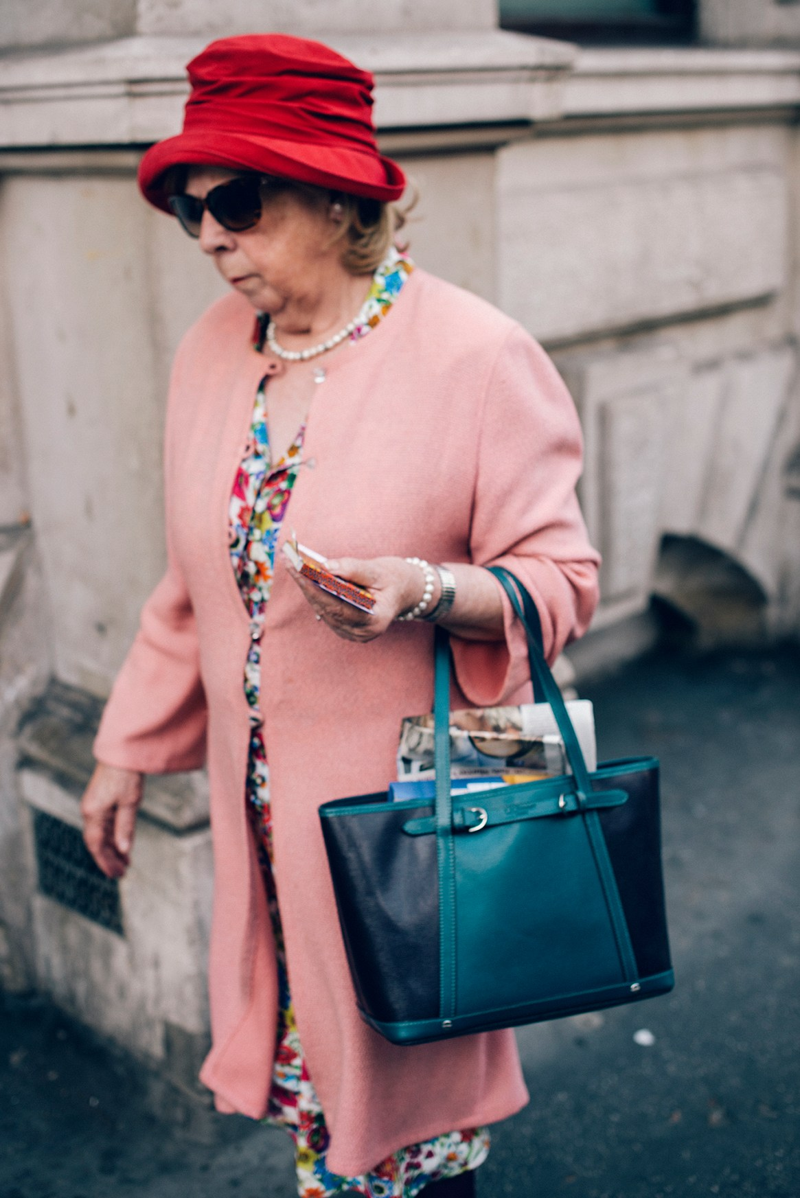 A woman wearing a vintage pink coat, floral dress, red hat, walks along the pavement in Barbican, London holding a small notebook and carrying a large handbag
