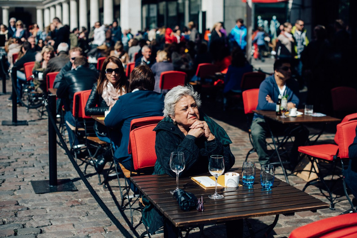 A woman sits alone at a table in a crowded restaurant on the piazza in Covent Garden, London