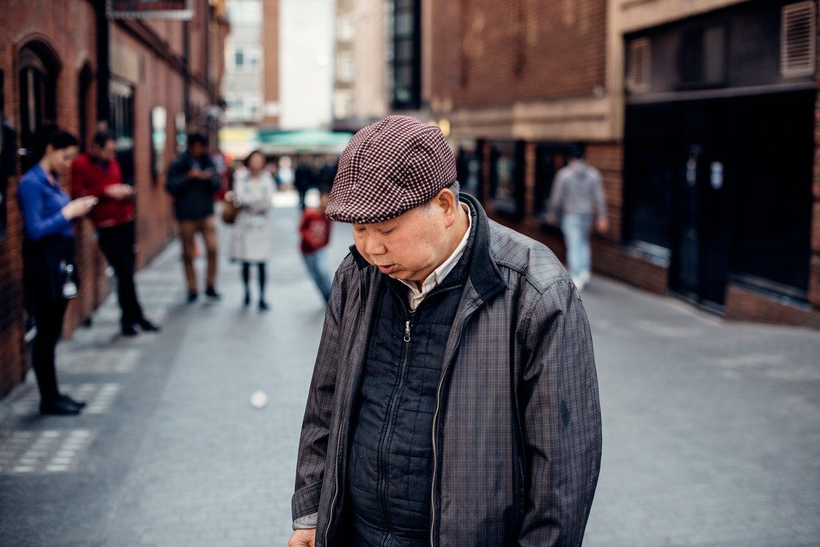 A man dressed in retro cap and jacket bows his head as he strikes a lonely pose in front of a group of people hunched over the mobile phones in Soho, London