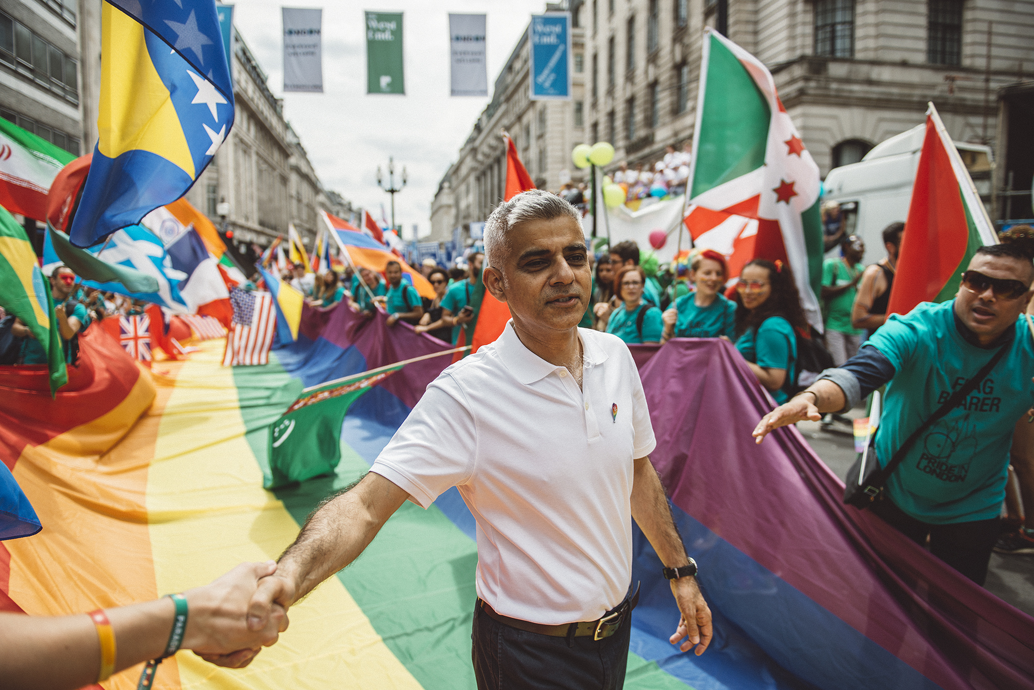 London Mayor Sadiq Khan surronded by cheering participants and colourful flags at the opening of the London Pride parade 2017