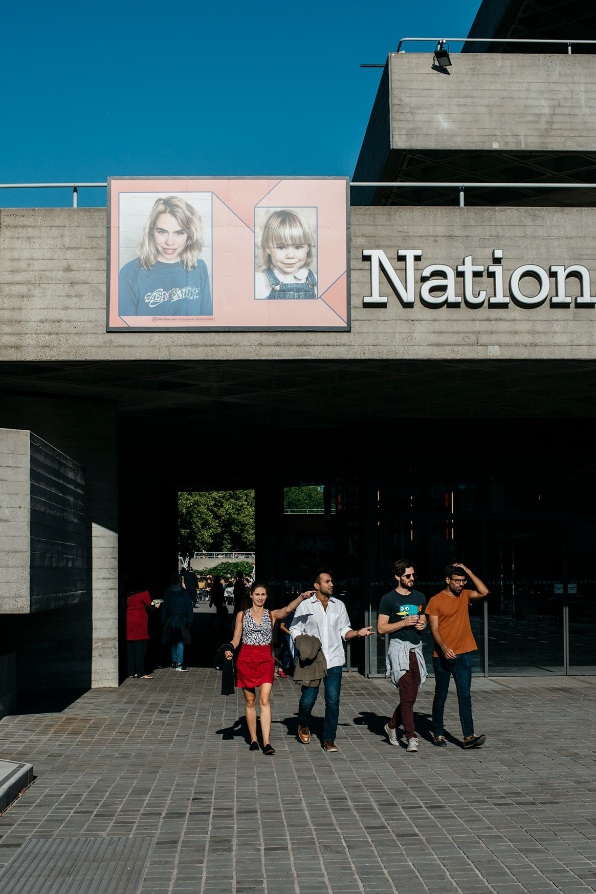 Two couples walk past a poster with portraits at the entrance to the National Theatre on the South Bank, London