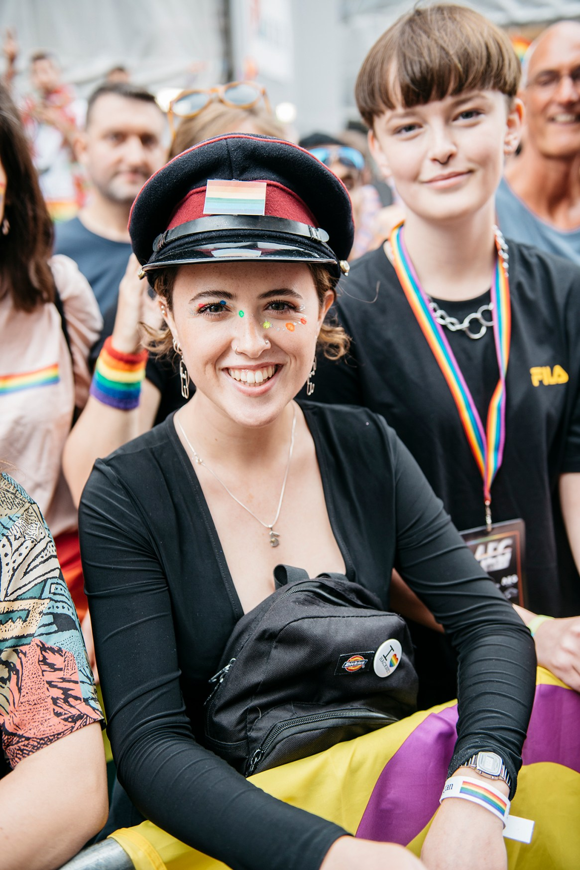 A woman wearing a black top and police style cap poses and smiles while watching the passing Pride in London parade, 2019.