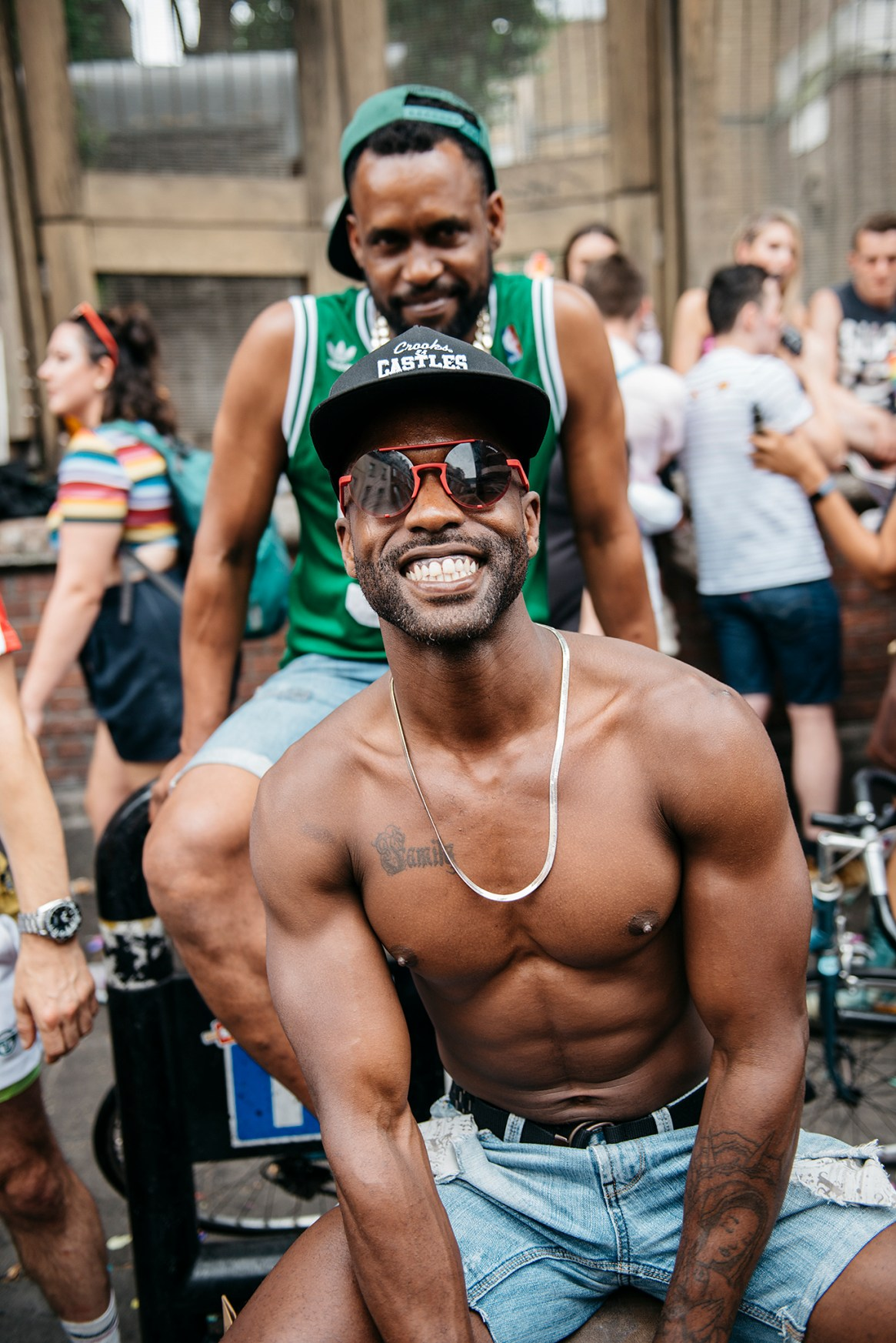 Two men smile and pose at the Pride in London 2019 afterparty in Soho