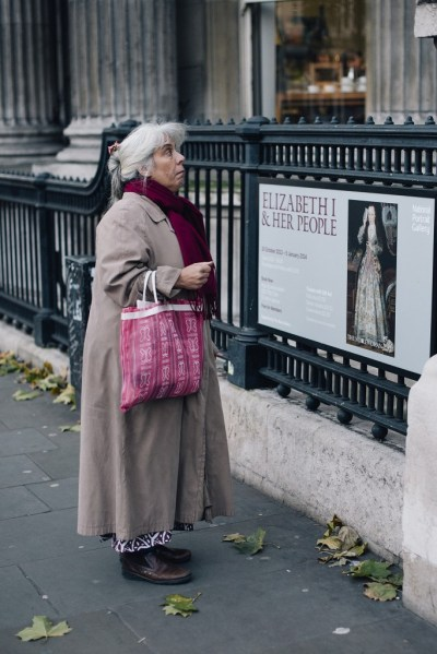 "Close-up of grey-haired woman with brown trenchcoat and pink bag posing in front of an exhibition poster reading ""Elizabeth I & her people"" outside the National Gallery on Charing Cross Road in London"