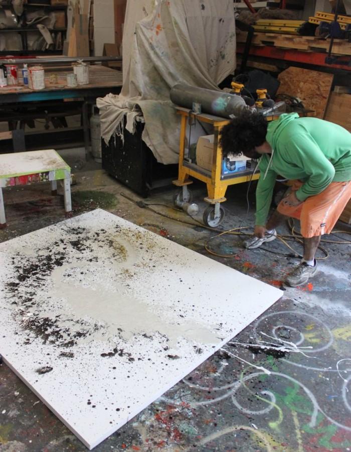 Aaron R. Thomas painting white polyurethane on canvas