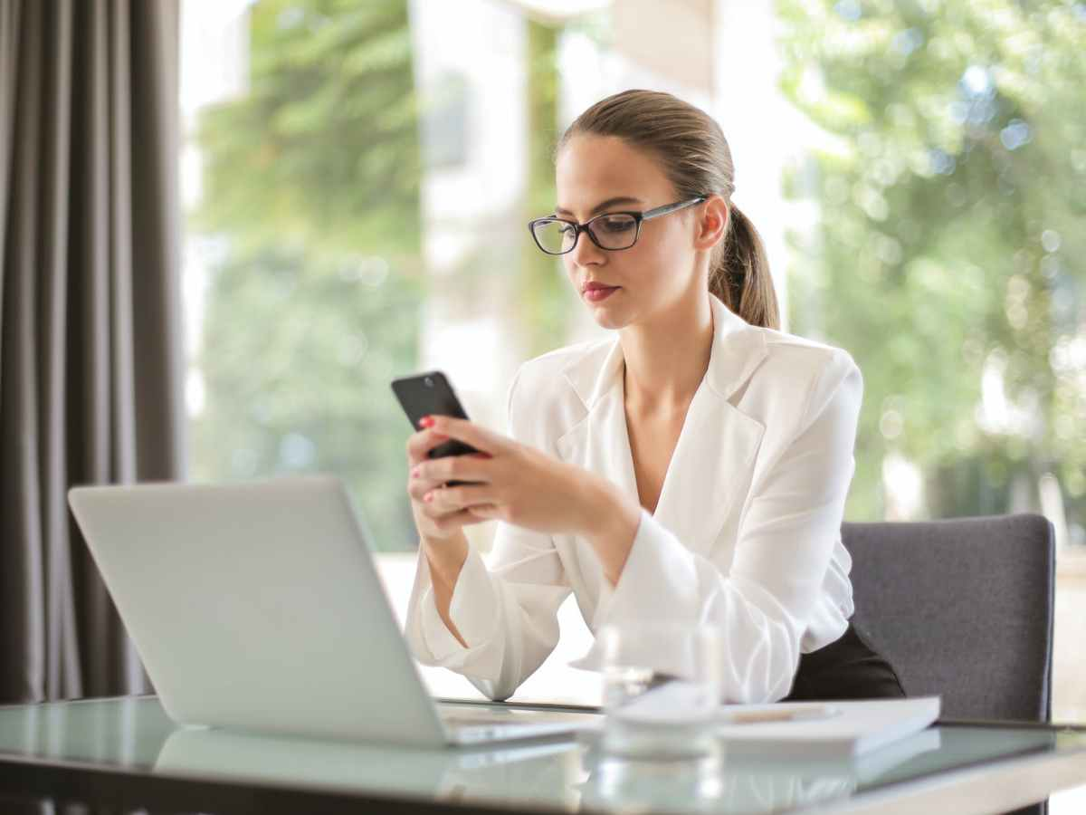 serious businesswoman using smartphone in workplace