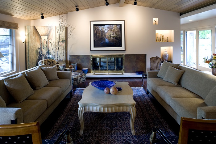 white coffee table between tan couch and beige couch in front of a gold fireplace above white slab
