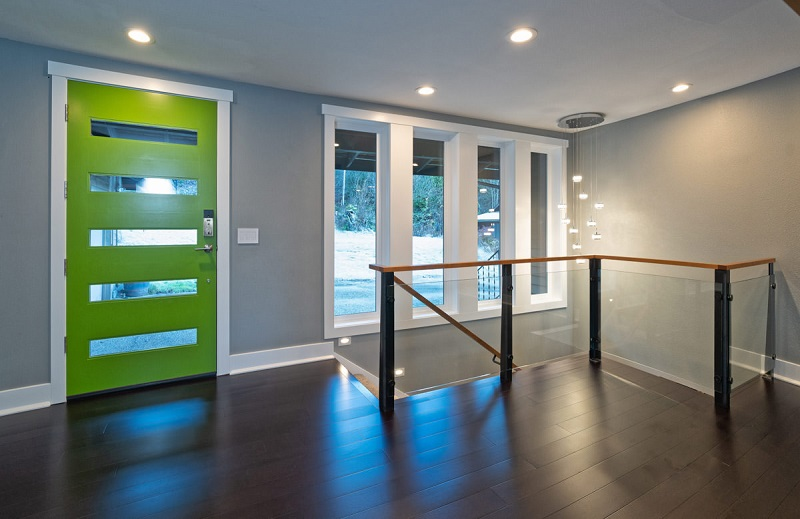 Bright green front door with glass handrail around stairs