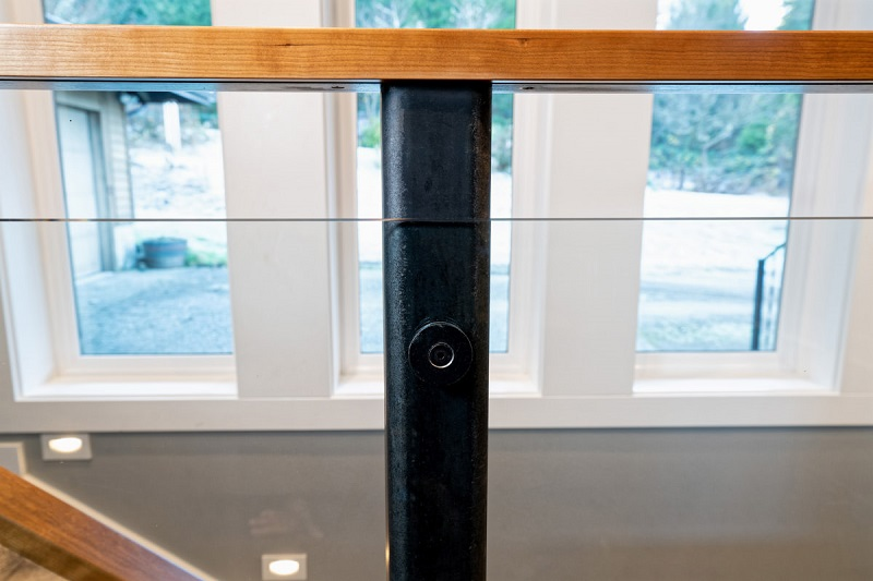 Bolt holding glass against metal handrail post with wood handrail