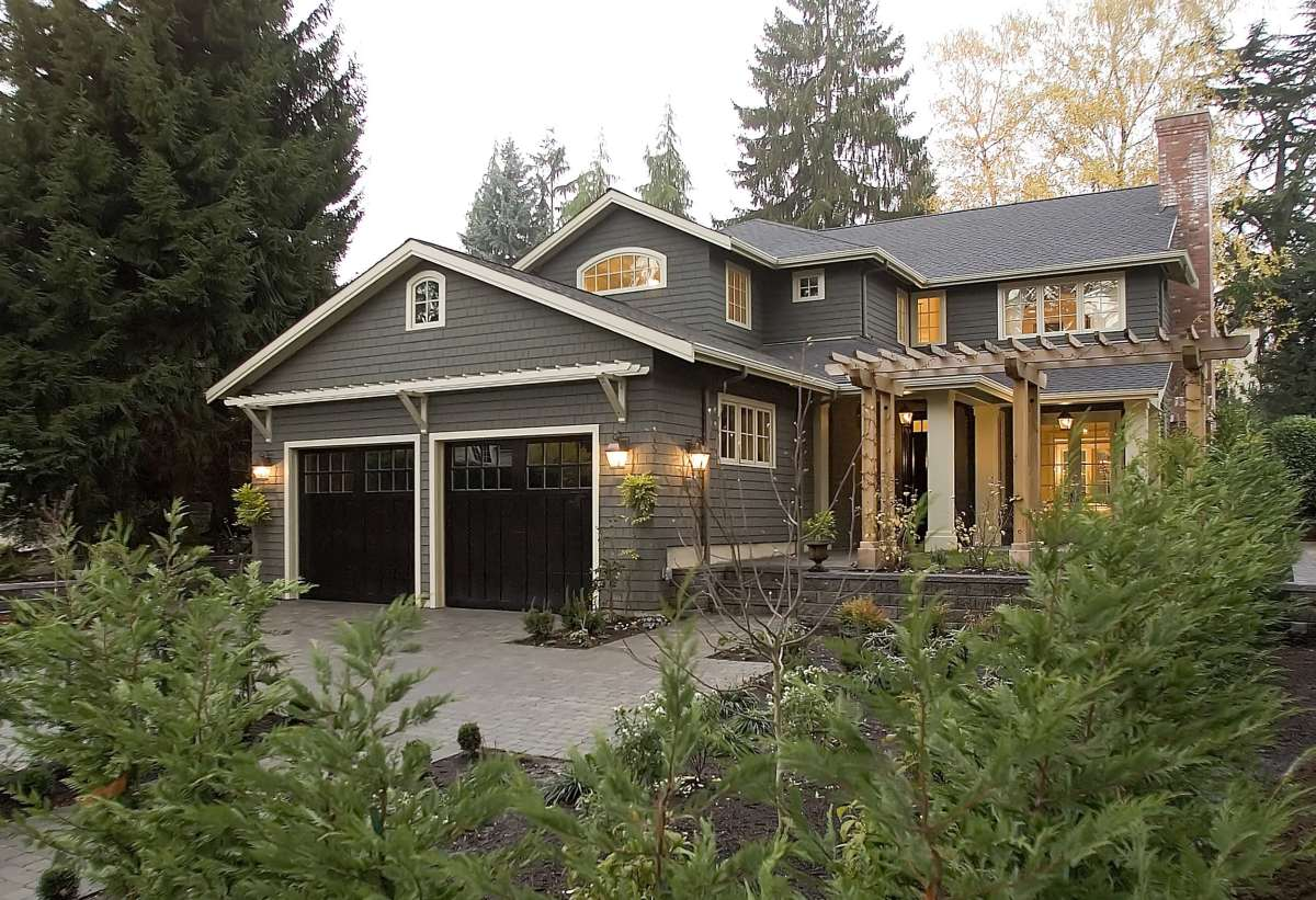 multi story grey shingled house with white trim behind a wall of green trees