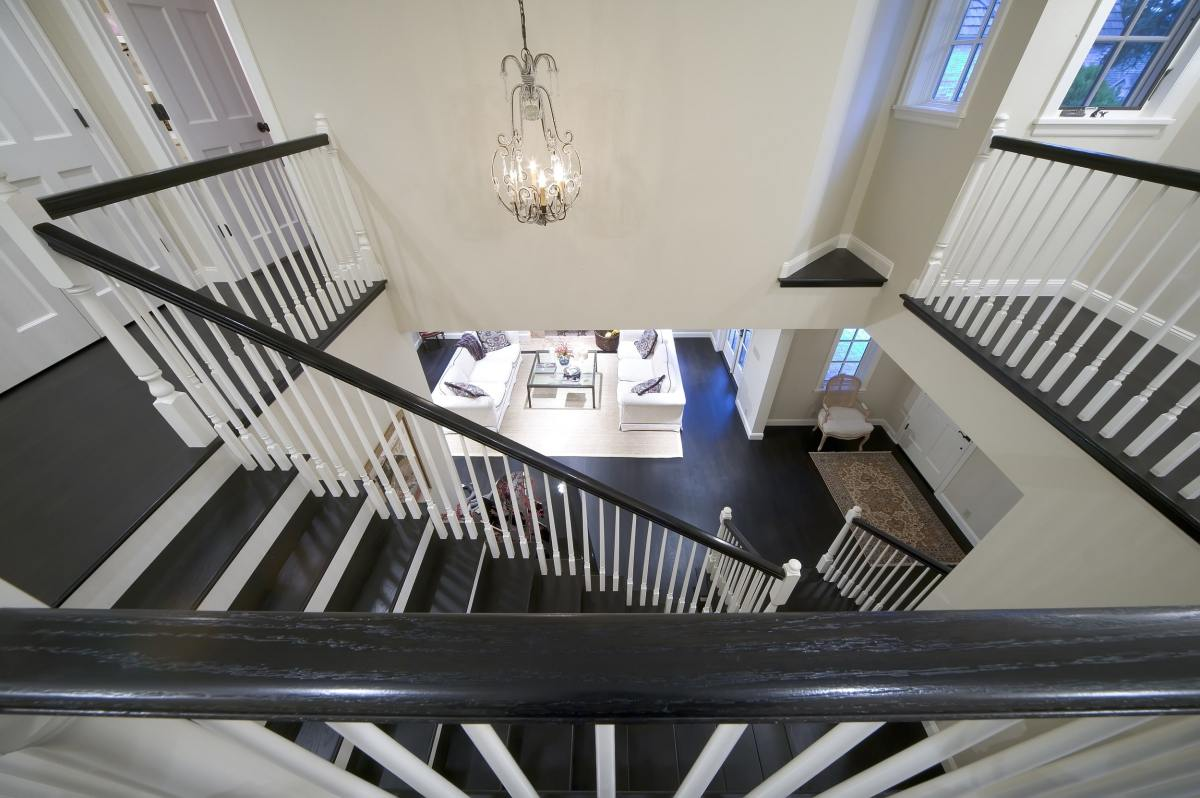 from upstairs looking down at a staircase over a black handrail
