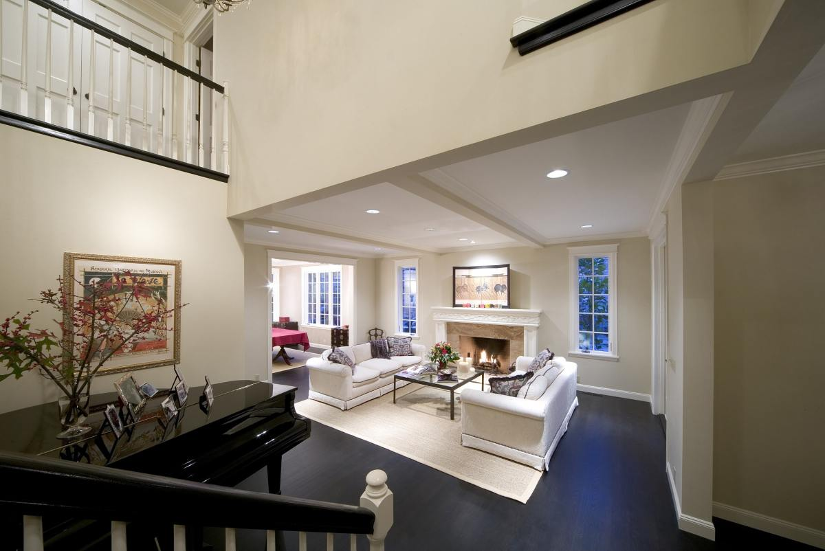 livingroom with two white couches and a glass coffee table in between in front of a fireplace
