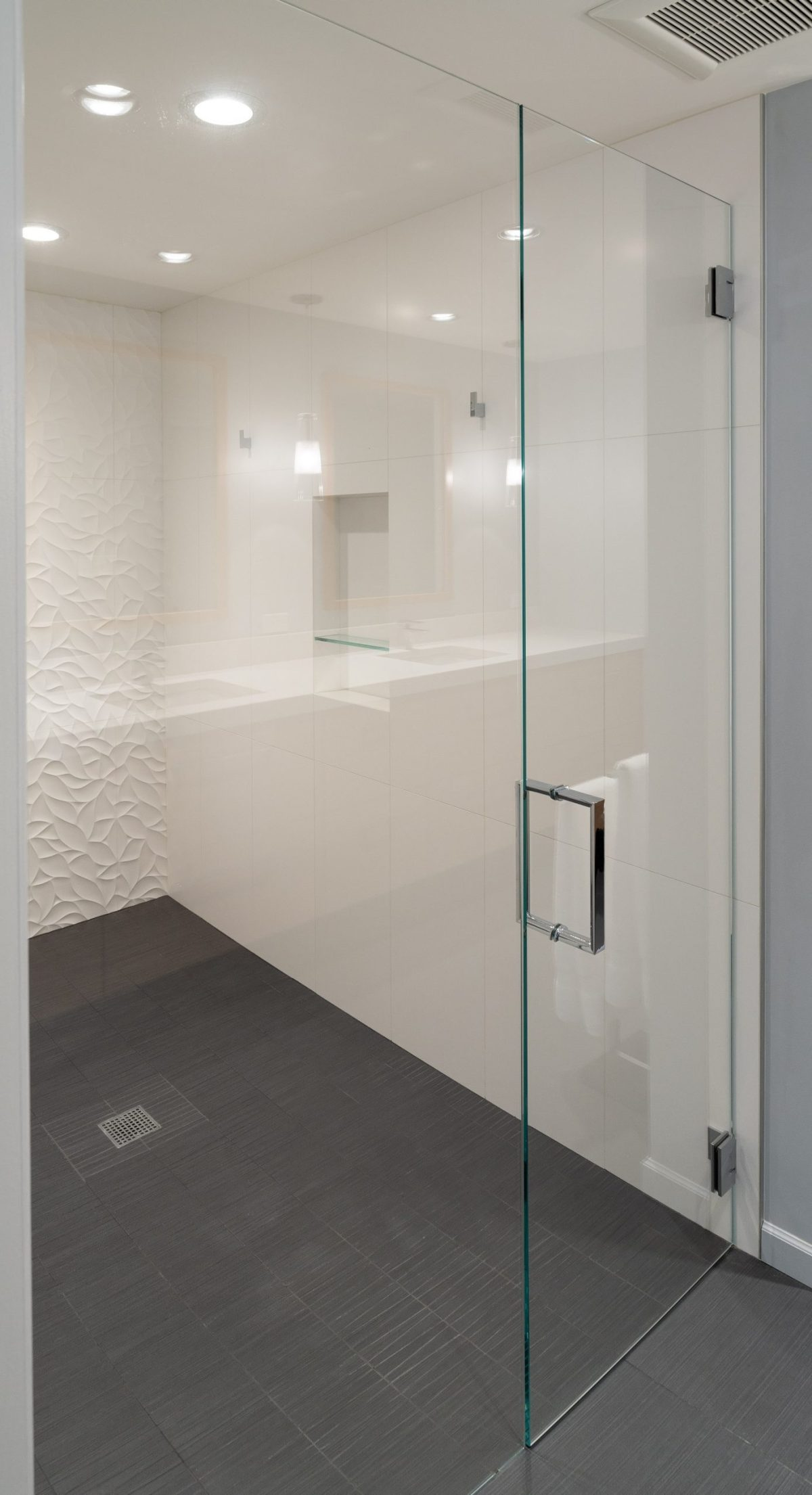 glass wall & door shower enclosure with white tile walls and grey floor tile