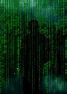 Bild: Schwarzer Umriss einer Person vor einer Wand aus Code beziehungsweise Sonderzeichen in grüner Schrift auf schwarzem Grund