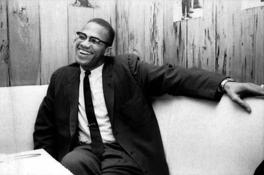American civil rights leader Malcolm X (1925 - 1965) laughs as he relaxes on a couch in a wood-panelled room, March 1964. (Photo by Truman Moore/Time & Life Pictures/Getty Images)
