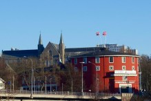 The Norwegian flag waving from the rooftop of Studentersamfundet.