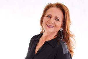 a mature woman with red hair looks happy to illustrate an article on Making Women Visible After Midlife