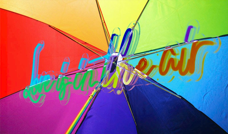 text 'Love is in the Air' superimposed on rainbow umbrella used for article 'Pan Means Pan - Falling In Love with the Universe'