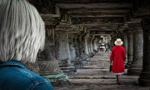Woman in red coat walking down tunnel towards photos of life. Image for Sexuality Down the Decades guest blog by DSimone Suessl