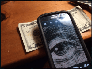 cell phone using macro lens hack to magnify five dollar bill