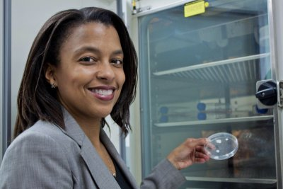 Image of Dr Treena Livingston Arinzeh in a laboratory looking at the camera holding up a culture.