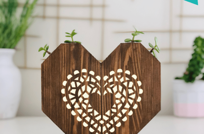 wooden heart with a heart mosaic painted on it