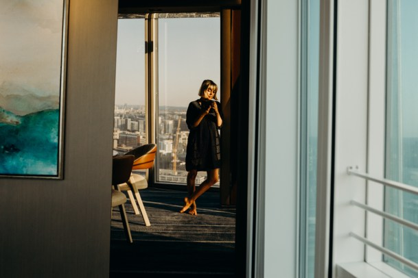 lifestyle photographers self portrait taken at the shangri-la hotel at the shard in london. She rests against the wall and warm sunlight kisses her face