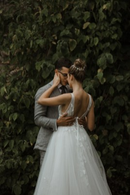 wedding photograph by stephanie green weddings. A low lit colourful portrait of a bride in a backless, white dress caresses the suited groom in front of a wall of leaves