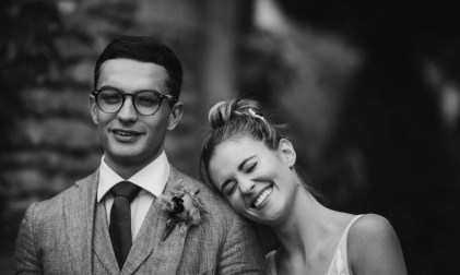 wedding photography by stephanie green. A black and white image of a smiling bride resting her head on grooms shoulder