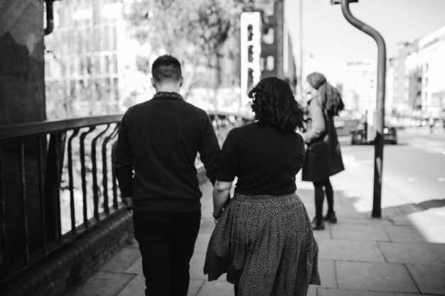 Black and white image of couple walking down a street