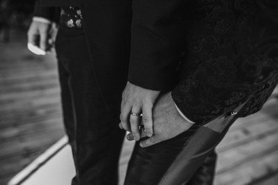 A black and white image of married couple holding hands