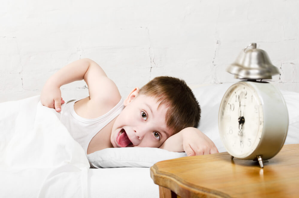 boy reaching for alarm after experiencing sleep anxiety