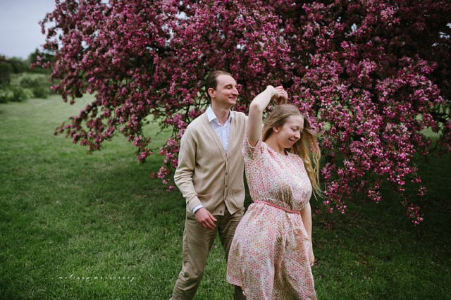 stephanie de montigny pink cherry blossoms photos ottawa melissa morrissey photography engagement photos, bride, blue eyes, curly blonde hair, stunning pink polka dot vintage dress, groom smiling natural cardigan leather elbow patches, dancing, swing jazz