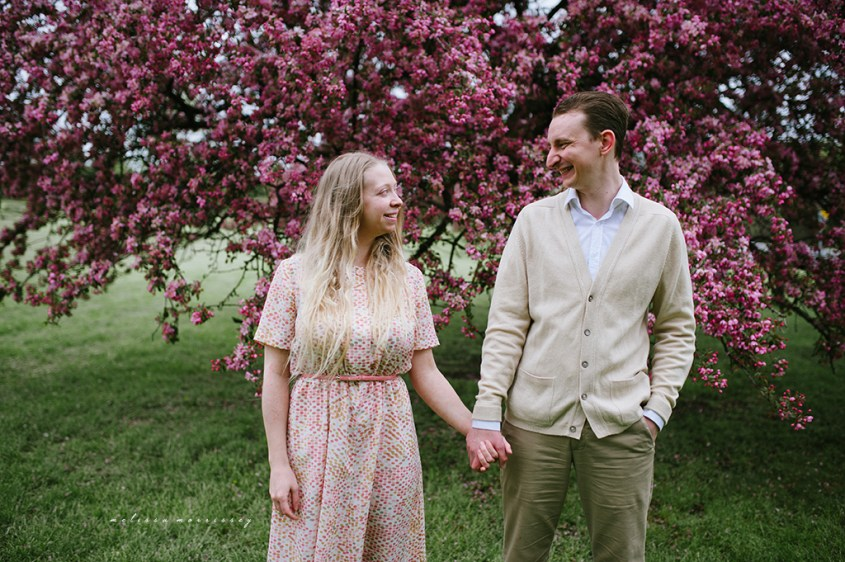 stephanie de montigny pink cherry blossoms photos ottawa melissa morrissey photography engagement photos, bride, blue eyes, curly blonde hair, stunning pink polka dot vintage dress, groom smiling natural cardigan leather elbow patches, holding hands