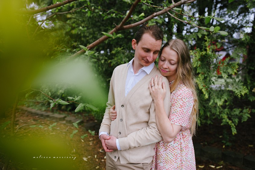 stephanie de montigny arboretum ottawa, magnolias, melissa morrissey photography, engagement photos, bride, blue eyes, curly blonde hair, stunning pink polka dot vintage dress, groom smiling natural cardigan leather elbow patches, hugging lovingly