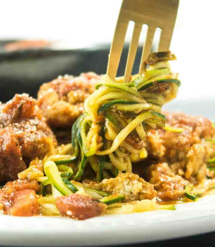 Zoodles with Cauliflower Meatballs being swirled with a fork